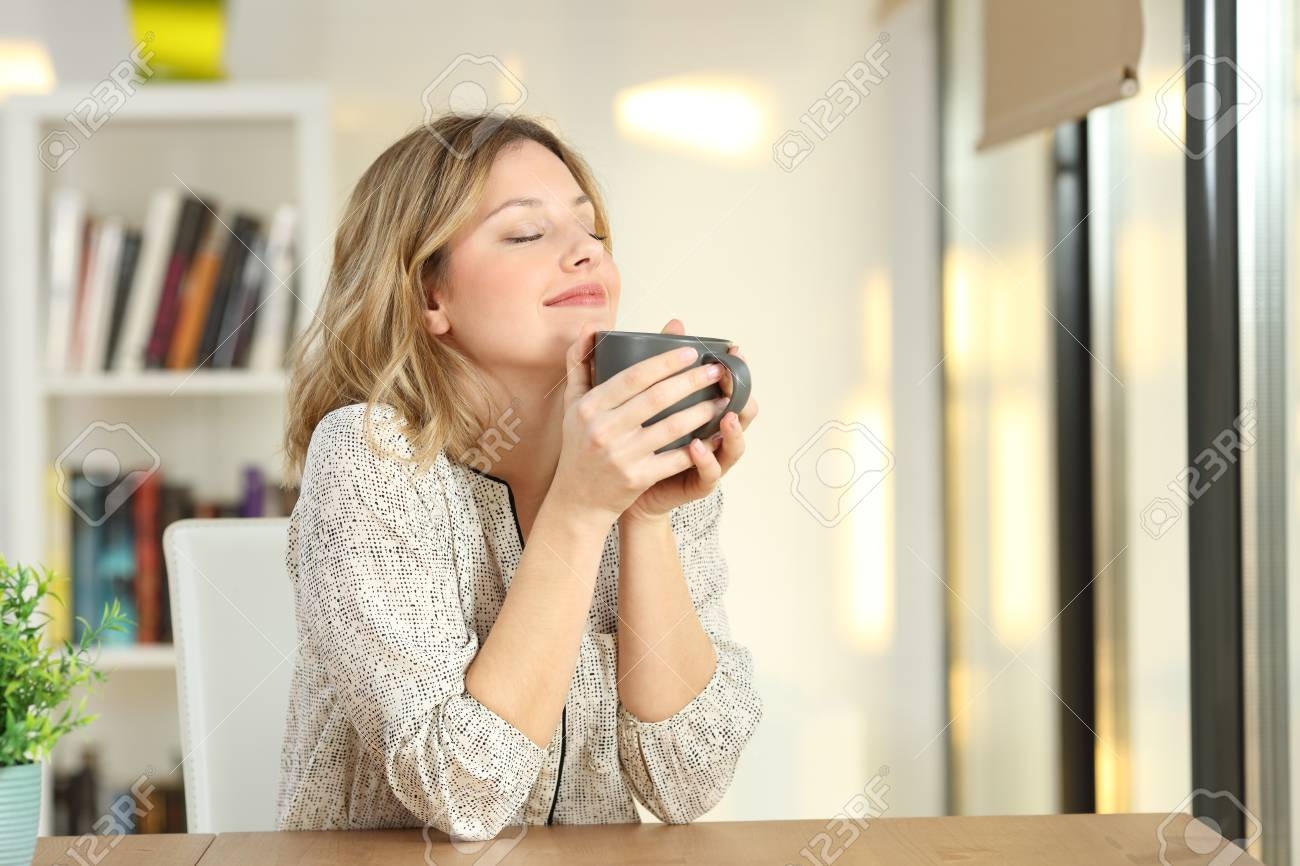 Portrait of a woman breathing and holding a coffee mug at home - 93080327
