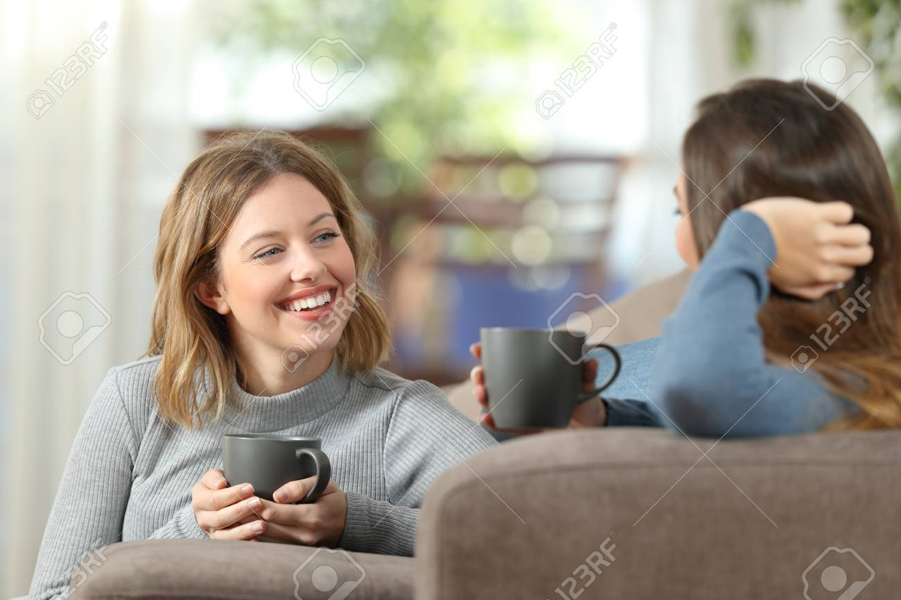 Two happy friends having a casual conversation sitting on a couch in the living room at home - 93048708