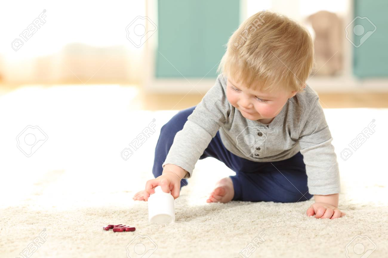 Baby In Danger Playing With A Bottle Of Pills On The Floor At Home Stock  Photo