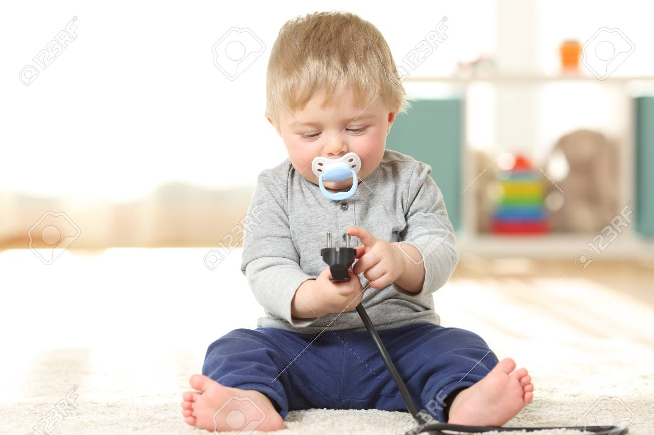 Fronf View Portrait Of A Baby In Danger Playing With An Electric Plug  Sitting On The