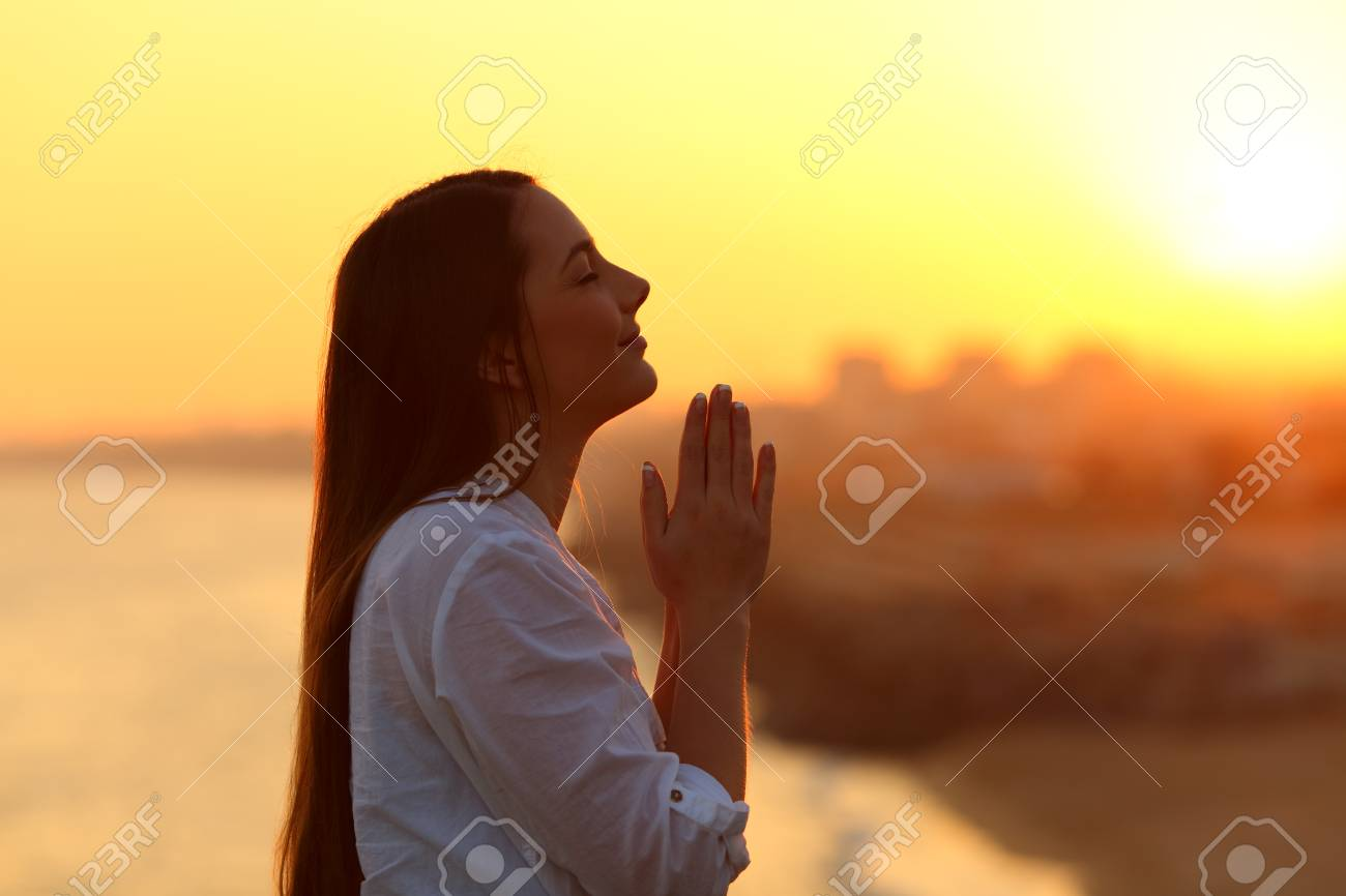 Side view backlight portrait of a woman praying and looking above at sunset - 95177738