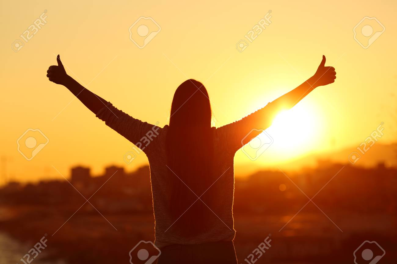 Back view backlight silhouette of a woman raising arms with thumbs up to the sun at sunset - 96101087
