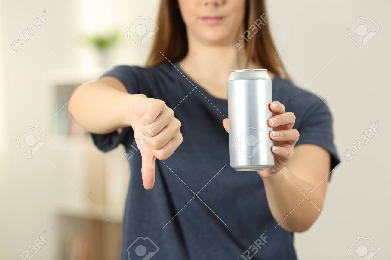 Front view close up of a woman hands holding a soda drink can with thumbs down at home - 101678231