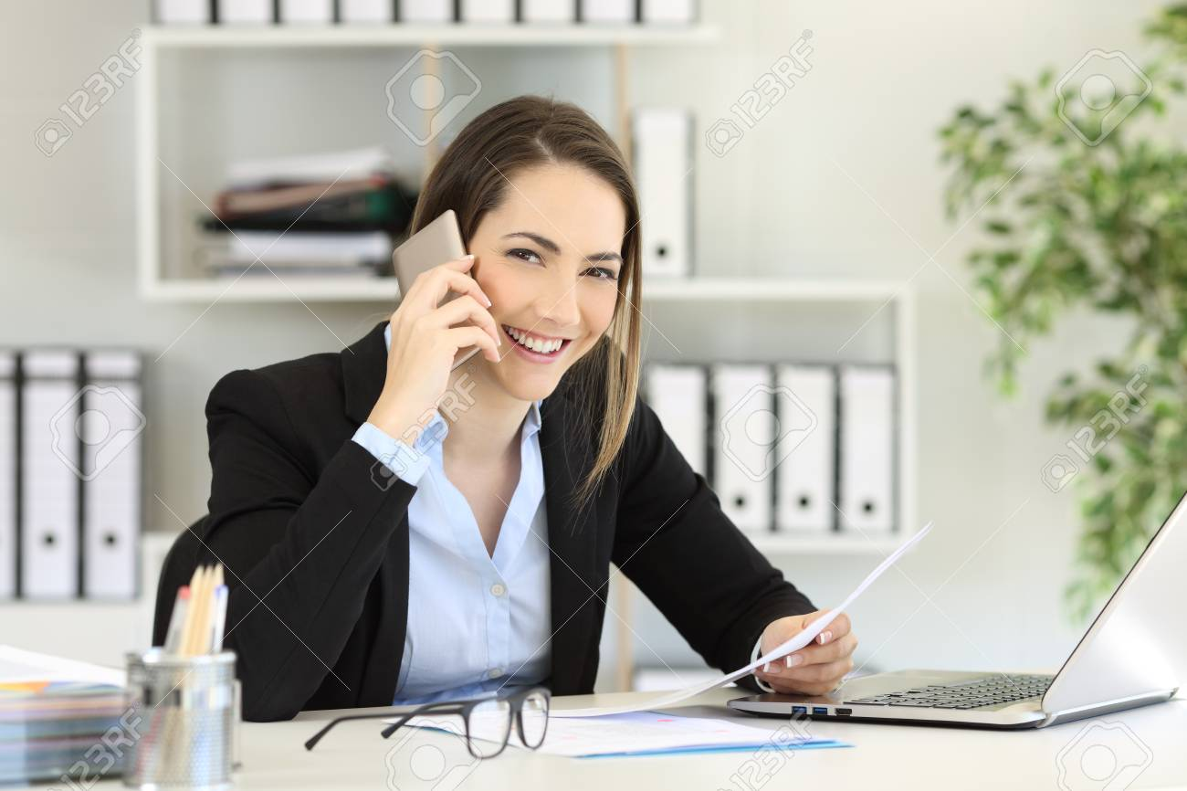 Happy Office Worker Calling On Phone Looking At You At Workplace Stock Photo Picture And Royalty Free Image Image 102076885