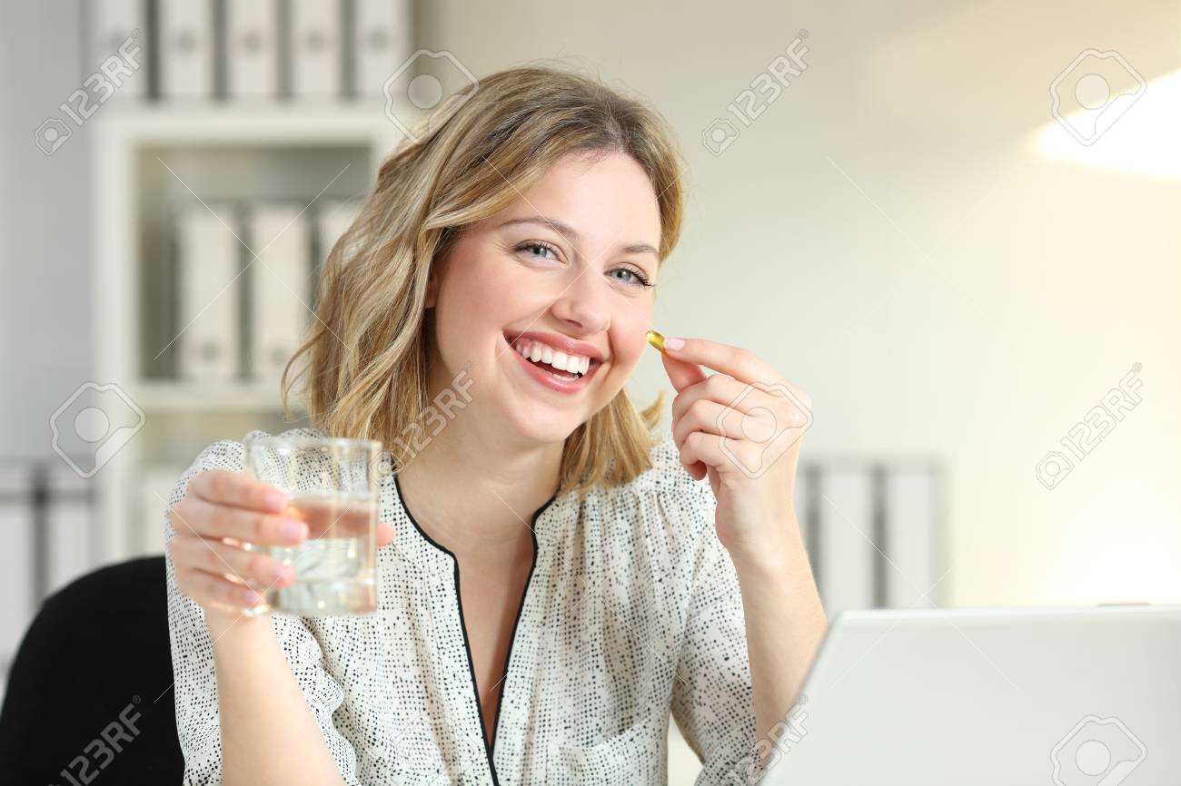 Happy office worker showing a vitamin supplement pill and a water glass looking at camera - 102077414