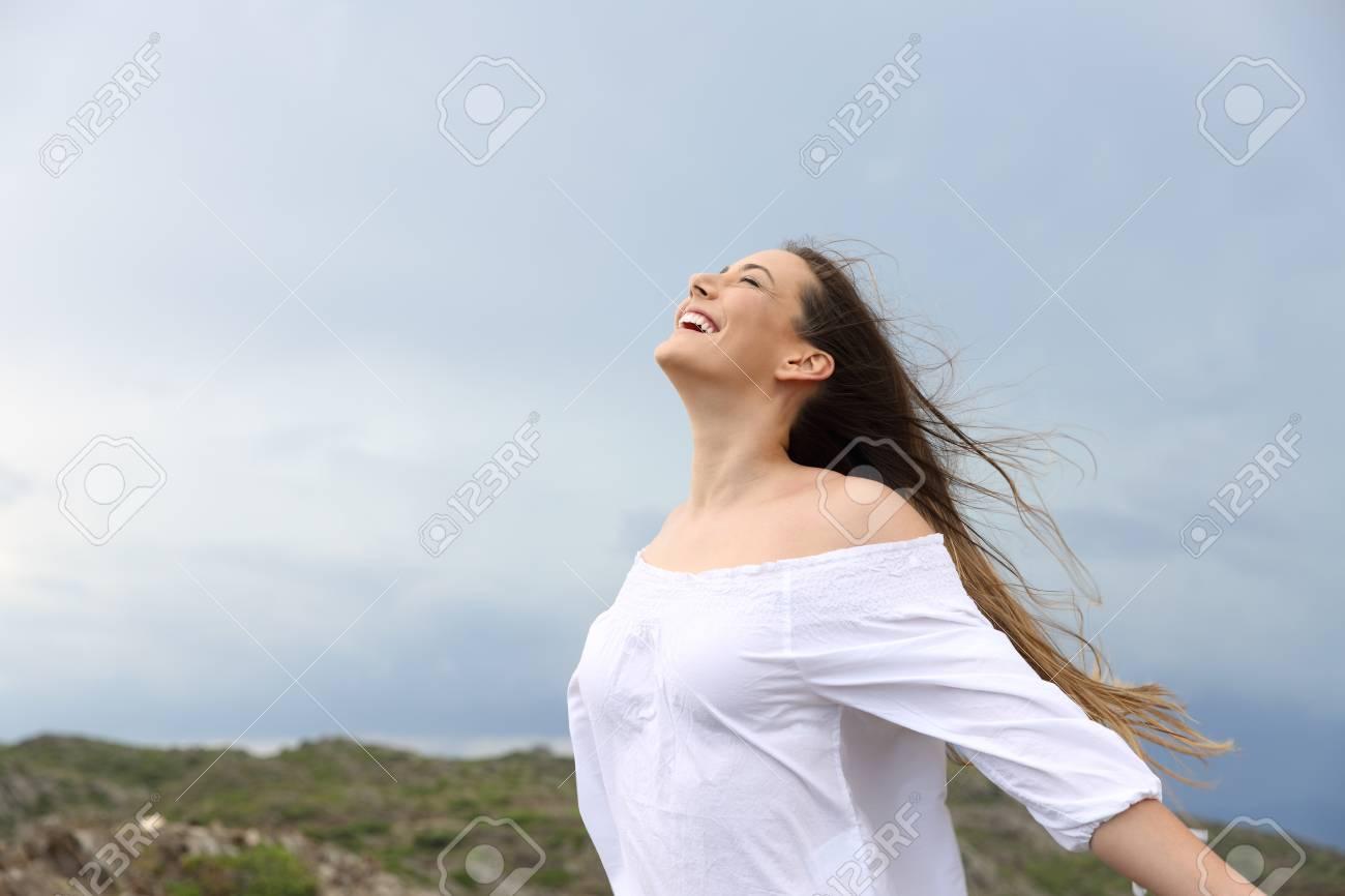 Positive woman breathing fresh air enjoying the wind - 103246649