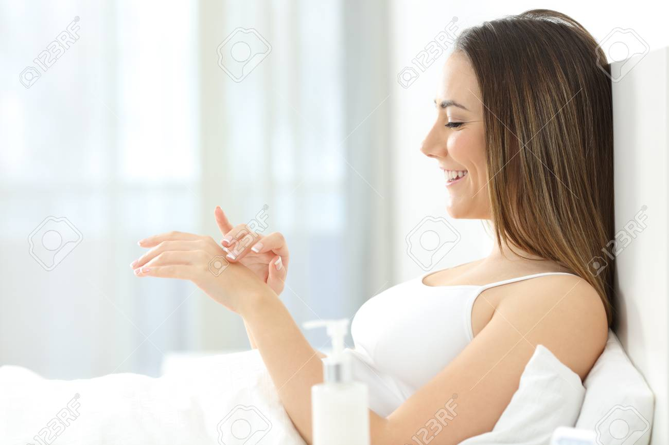 Side view portrait of a happy woman applying moisturizer cream on hands in a bed - 105199262
