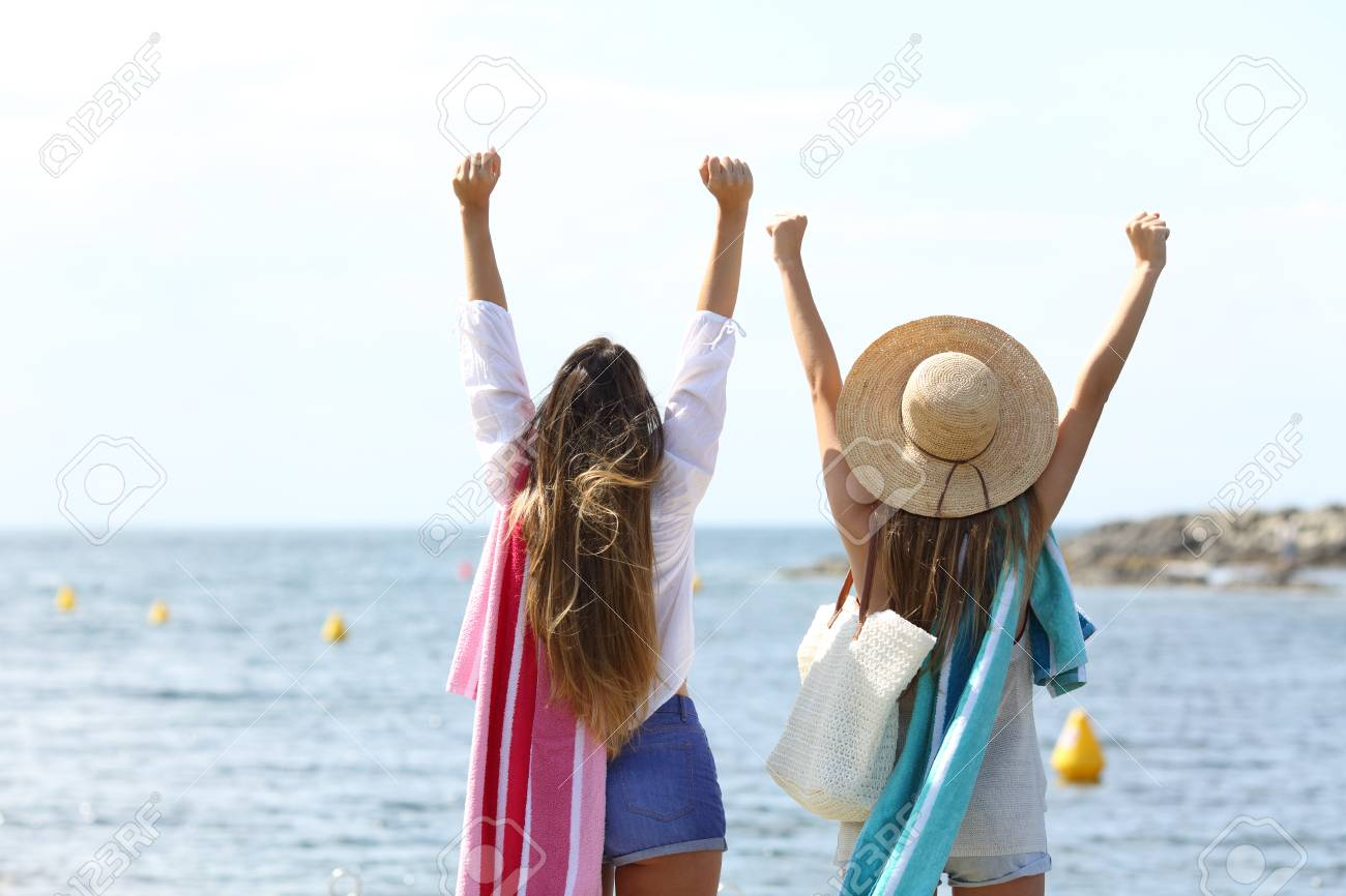 back view portrait of two excited tourists raising arms celebrating