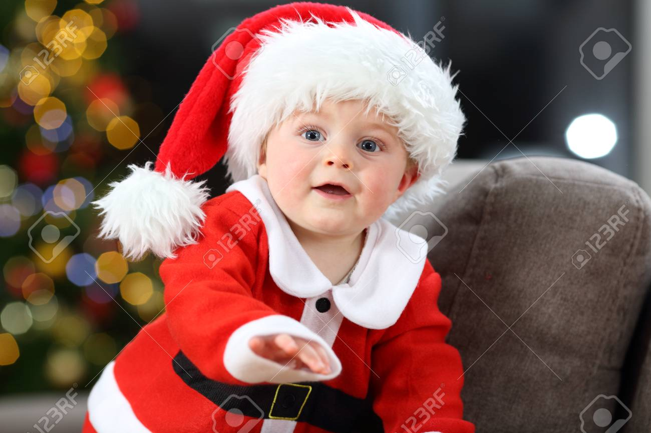 Cute baby wearing santa claus costume on a couch at home in christmas stock photo