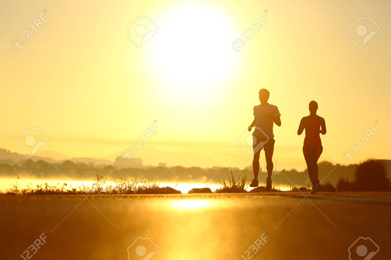 Man and woman silhouettes running at sunrise in a coast road - 109772753