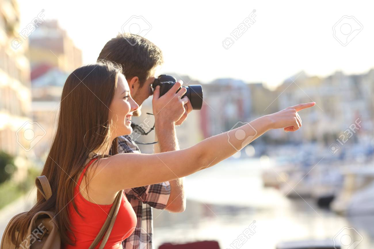 Two happy tourists sightseeing and taking photos with a dslr camera outdoors on vacation - 109800720