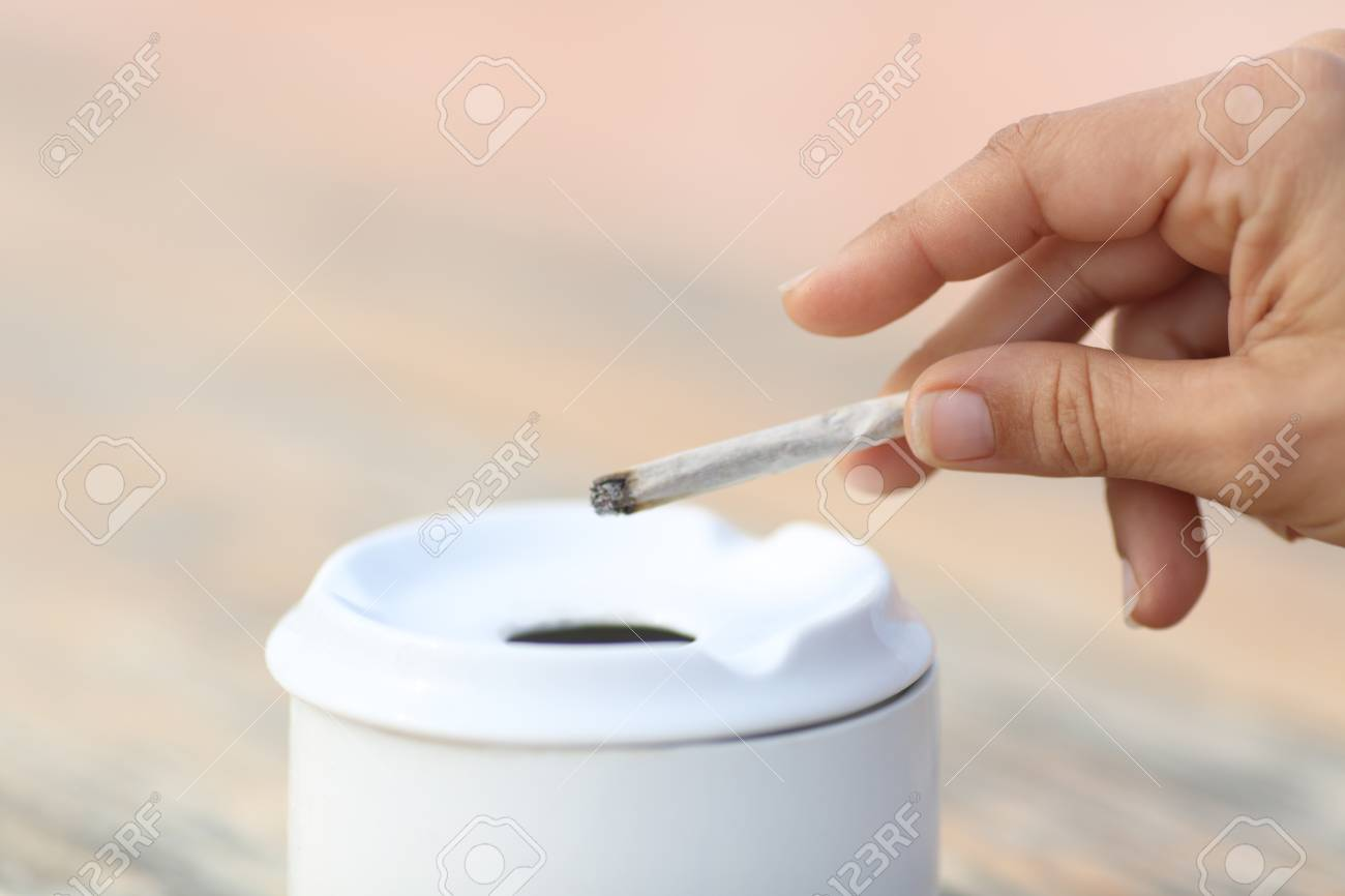 Close up of a woman smoking holding a hand made cigarette throwing the ash into the ashtray - 109890208