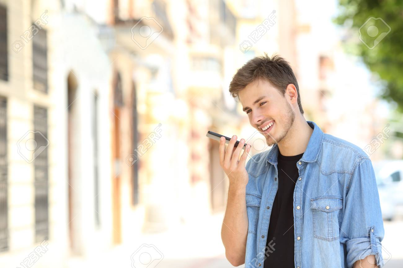 Happy boy using voice recognition on a smartphone in the street - 111427193