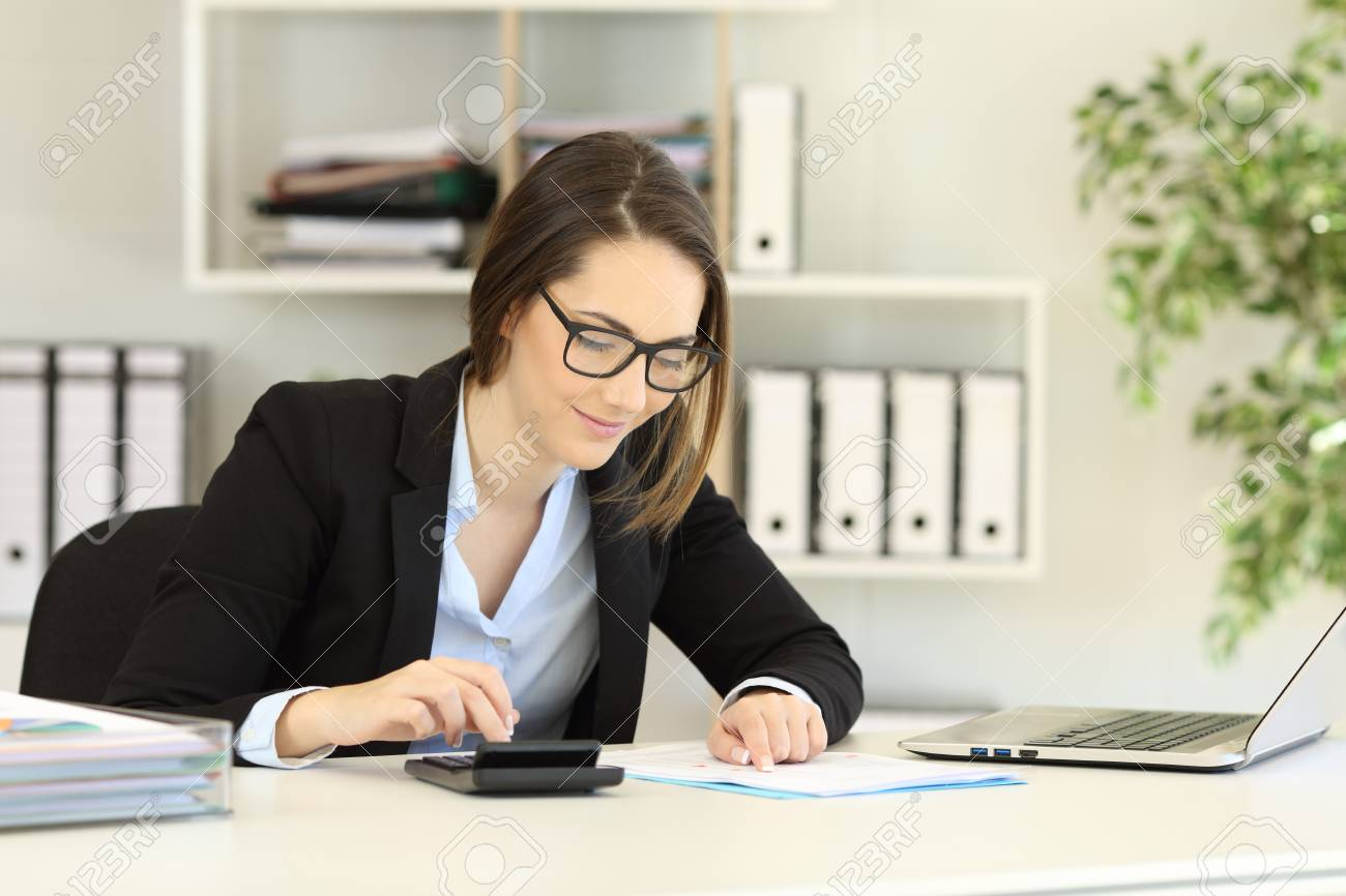 Office worker wearing eyeglasses doing accounting on a desk - 112439764