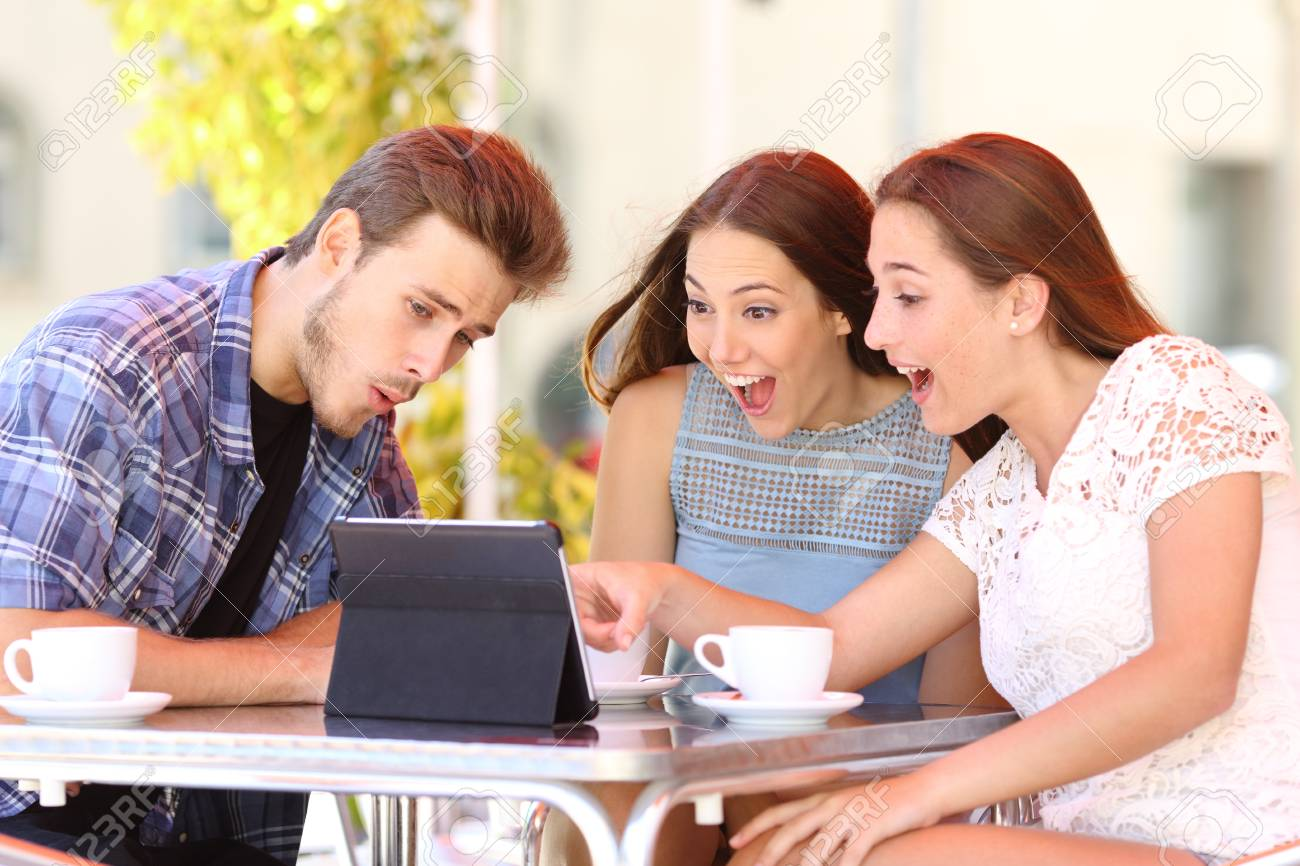 Three excited friends watching tablet content sitting in a coffee shop - 114073577