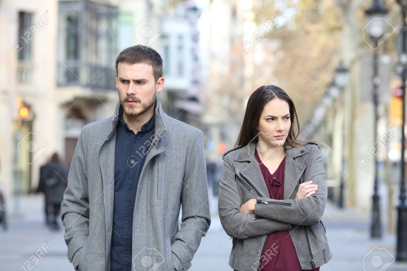 Front view portrait of an angry couple walking in the street after argument - 115370815