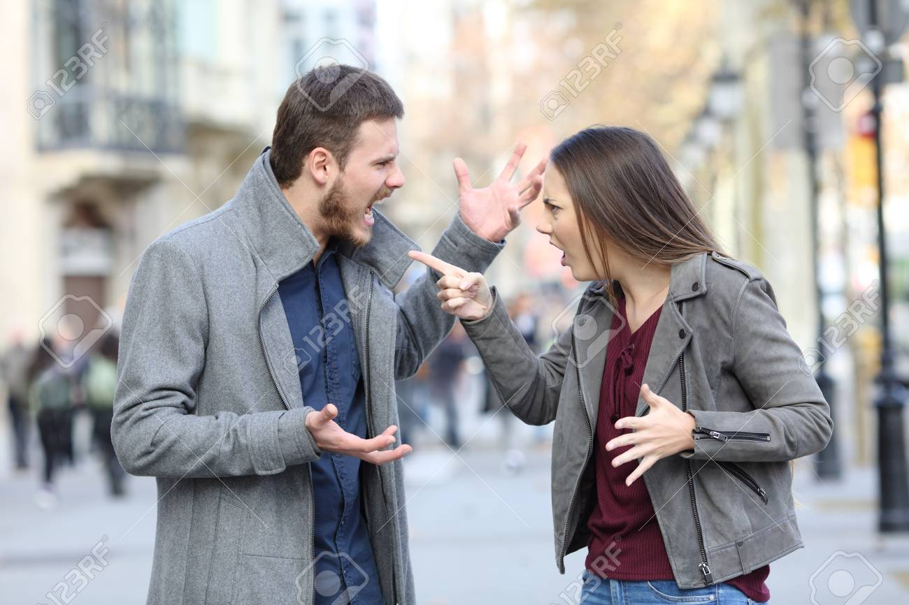 Angry couple arguing in the middle of a city street - 115370895