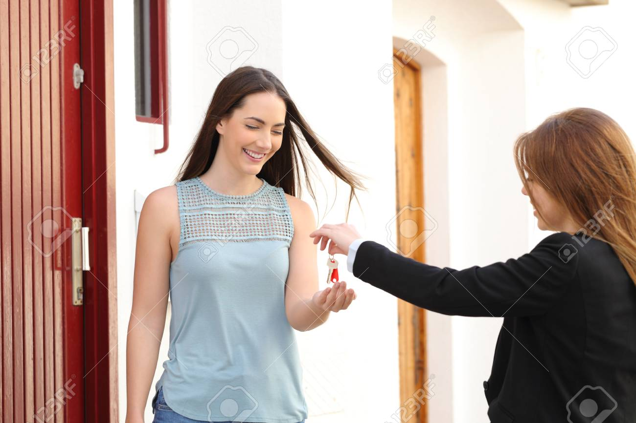 Happy tenant receiving apartment keys from real estate agent in the street - 115371150