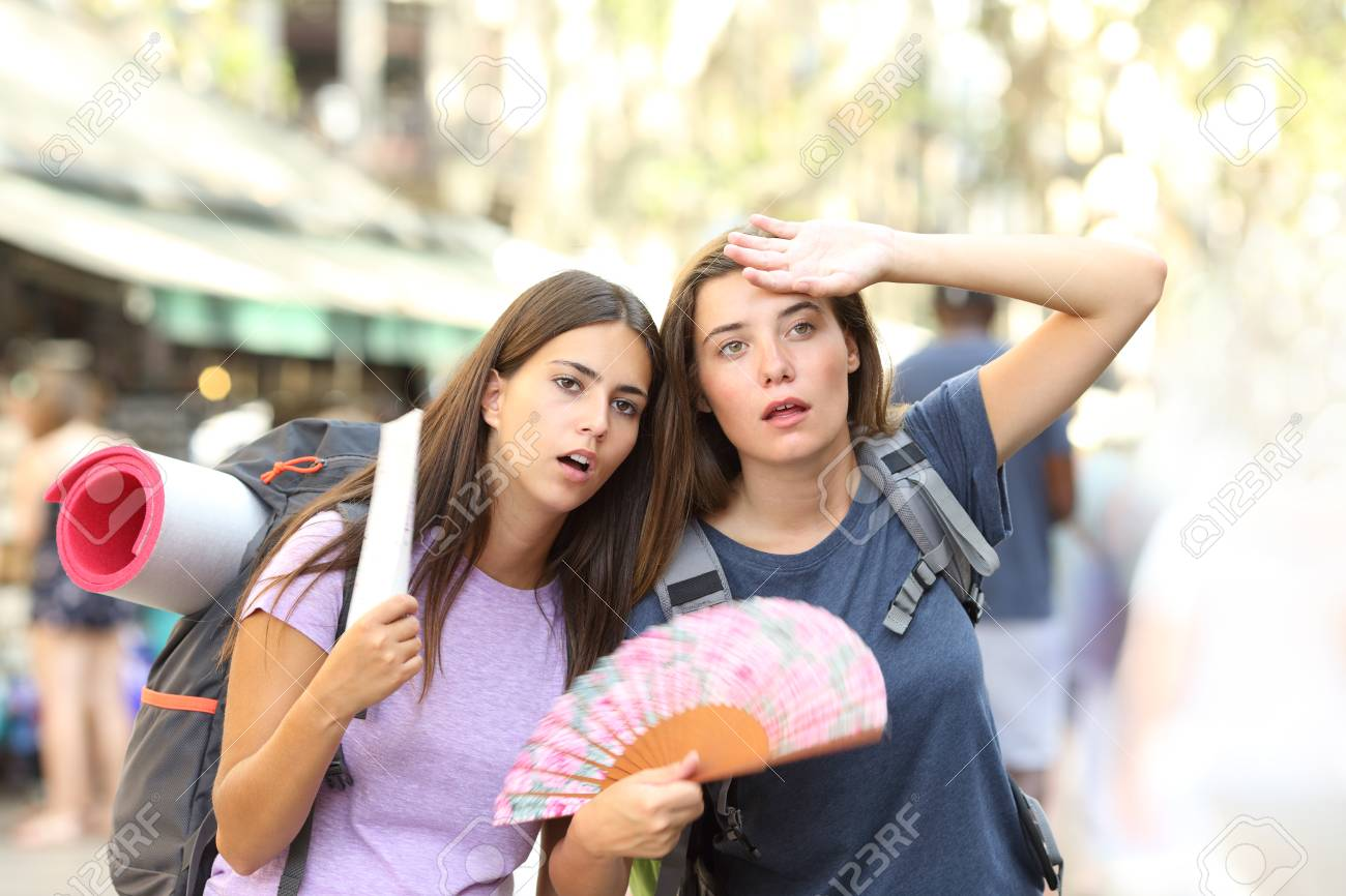Two backpackers suffering heat stroke walking on the street and fanning on summer vacation - 116123646