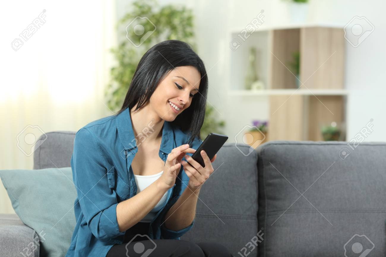 Happy woman using a smart phone sitting on a couch in the living room at home - 116123948