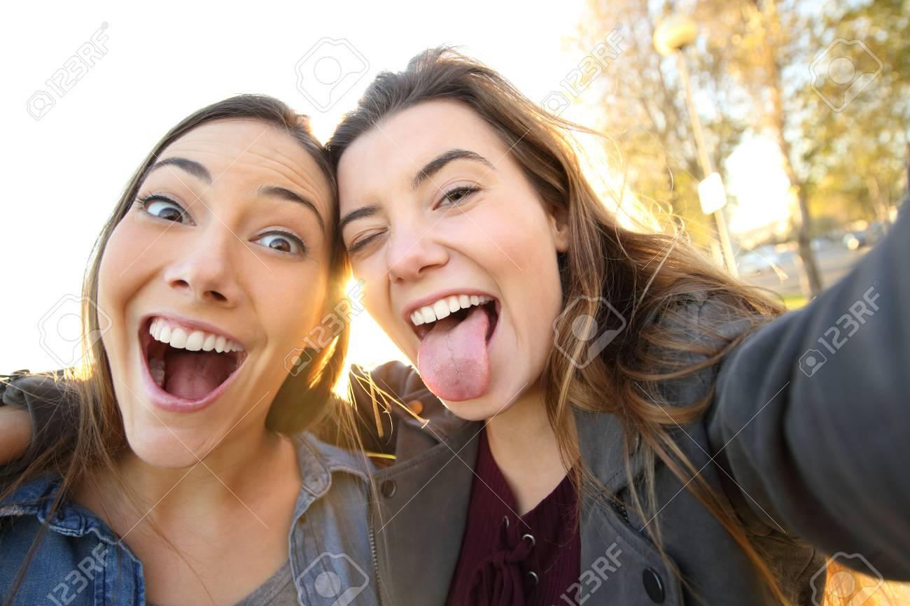 Two funny women joking taking selfies looking at camera in the street - 117941999