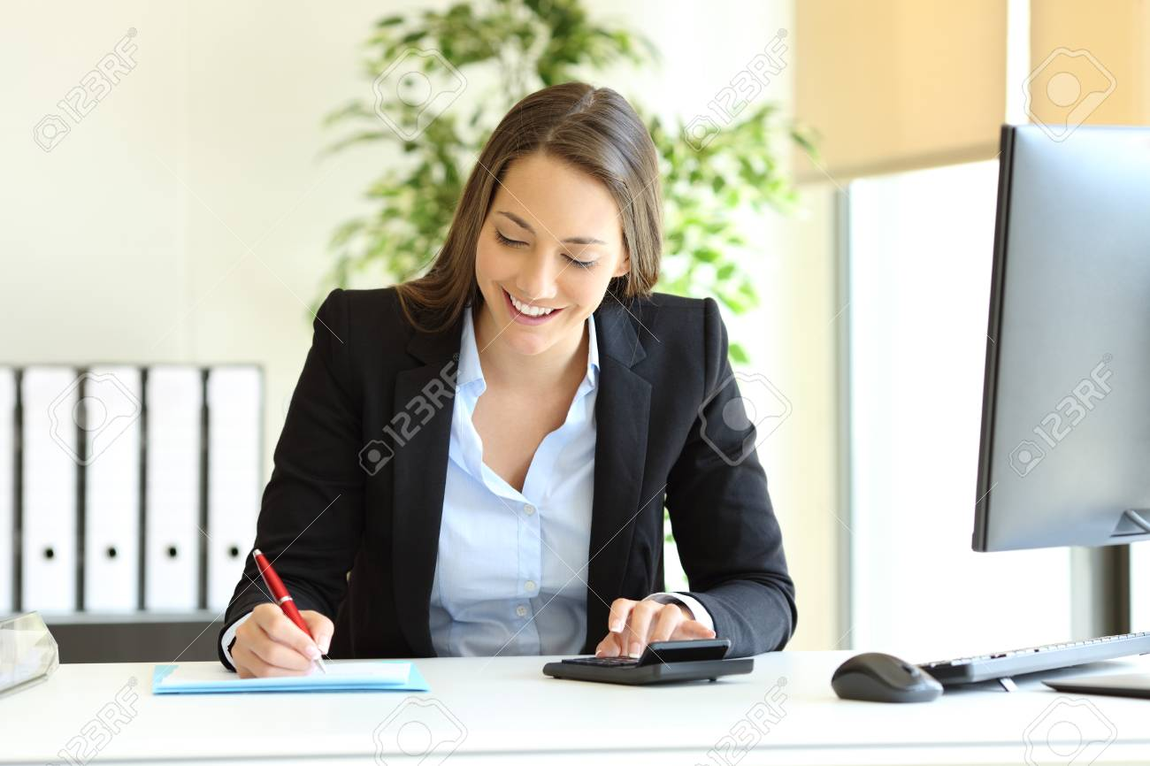 Office worker calculating budget using calculator and writing on a document - 117941869