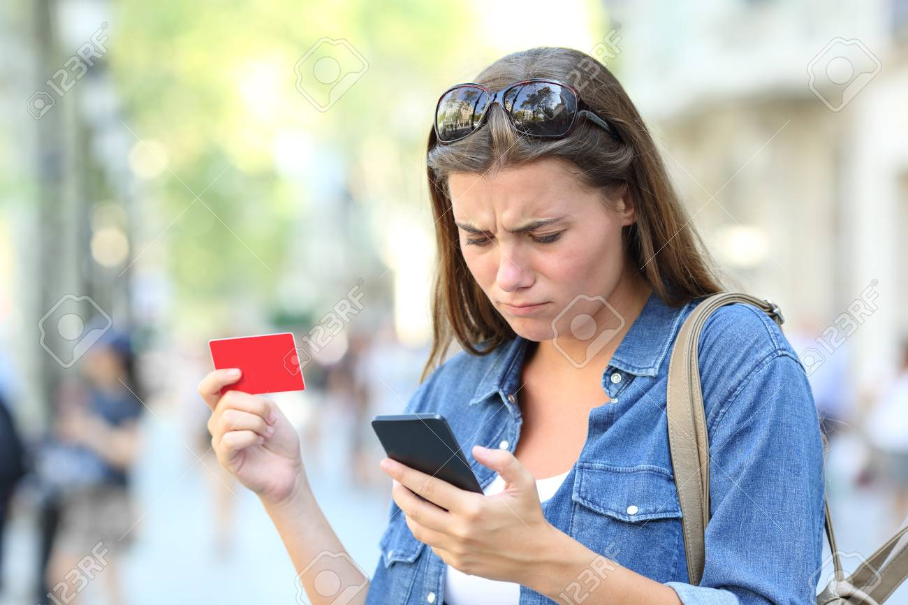 Worried girl having problem paying online with credit card and smart phone in the street - 117941880