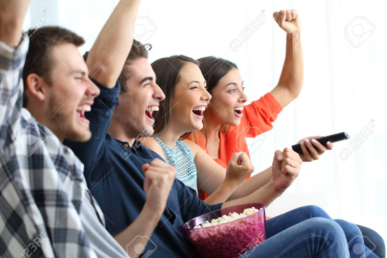 Four excited friends watching tv celebrating success sitting on a coucn at home - 117941916