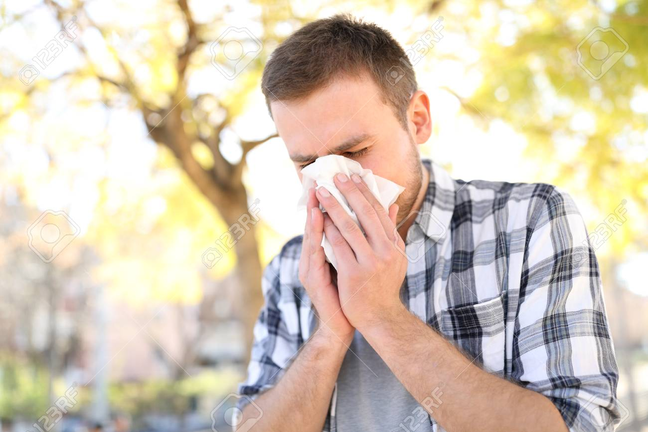 Allergic man sneezing covering nose with wipe in a park in spring season - 117941963