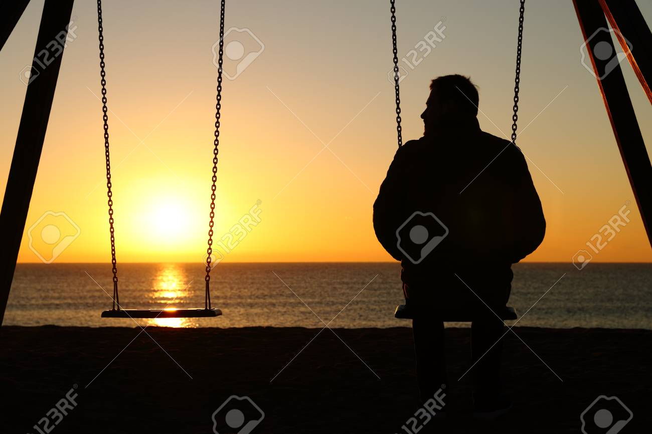 Back view backlighting silhouette of a man alone on a swing looking at empty seat at sunset on the beach in winter - 117963685