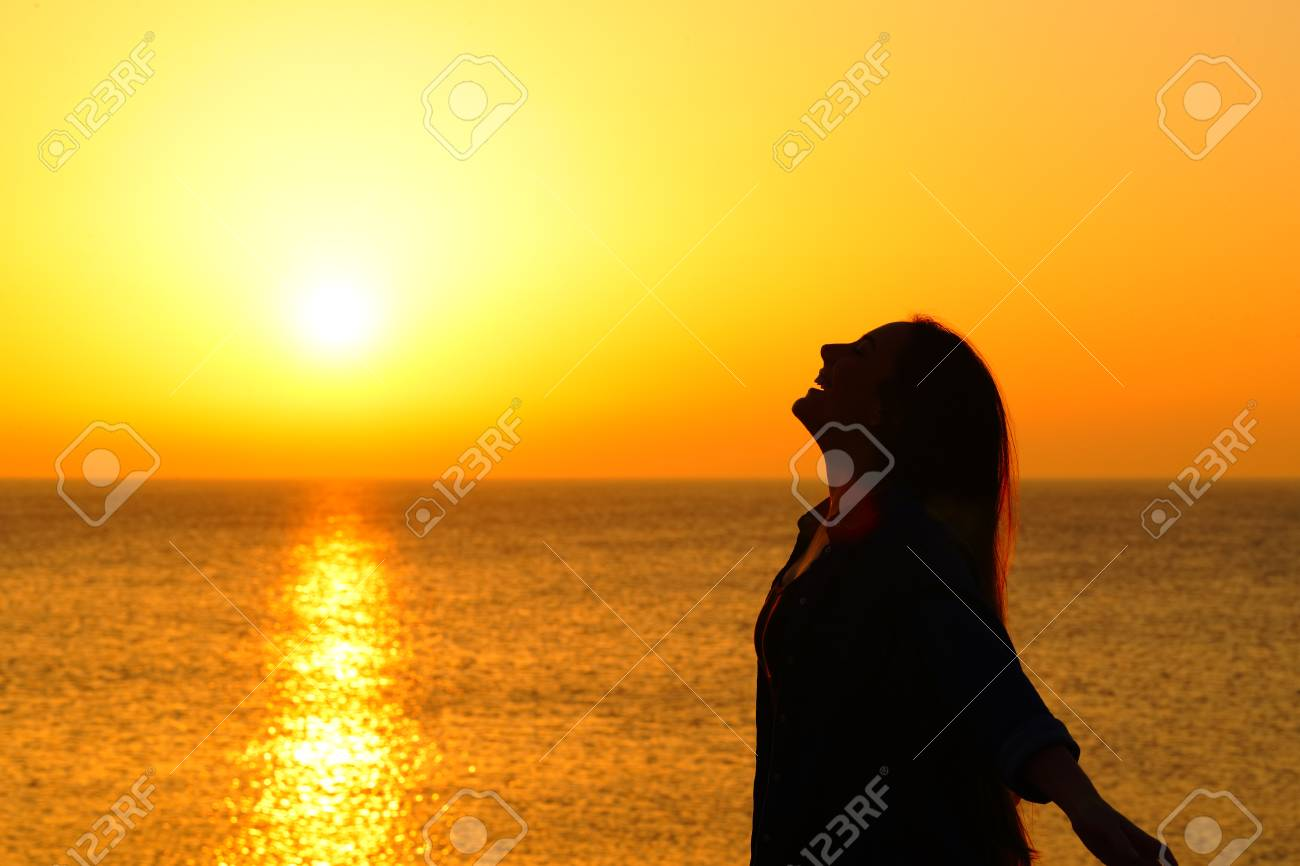 Side view portrait of a happy woman silhouette on the beach breathing at sunset - 119003201