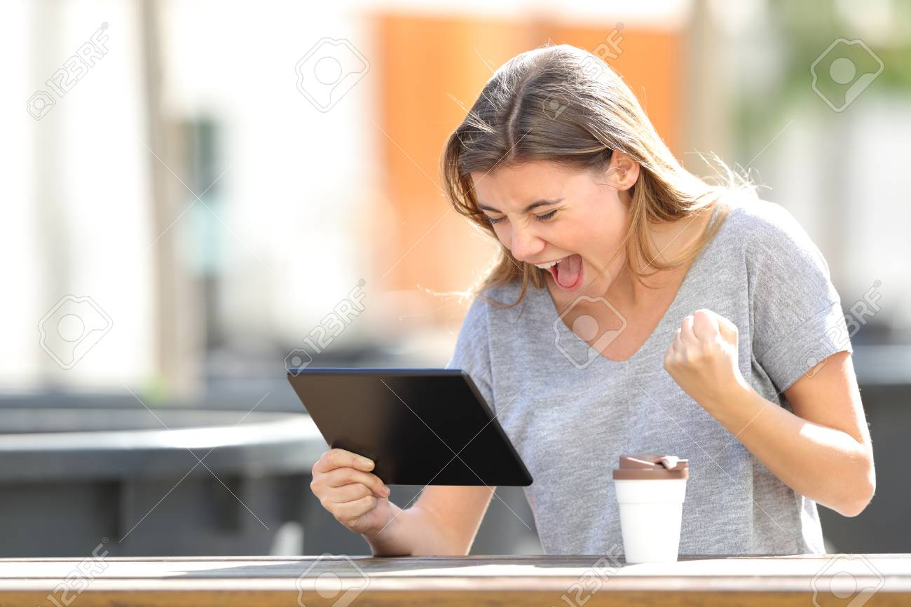 Excited girl finding online content in a tablet sitting in a park a sunny day - 119003950