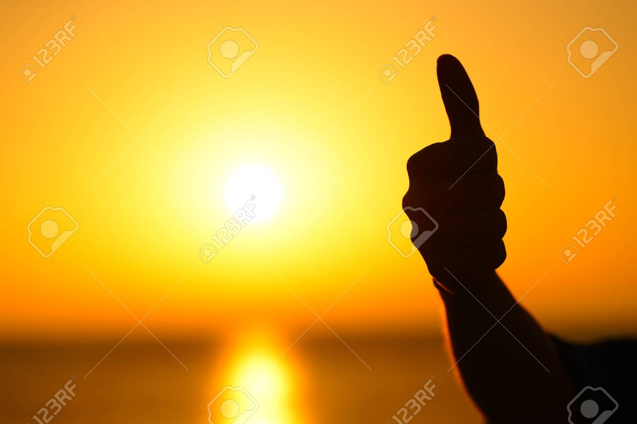 Close up of a woman hand silhouette gesturing thumb up at sunset with a warm sun in the background - 119003983