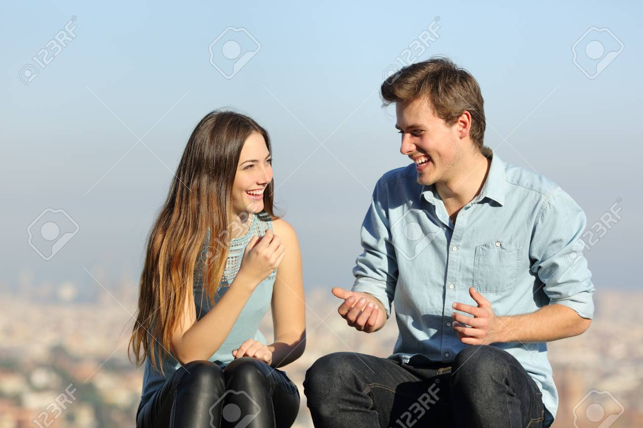 Happy couple talking sitting in a city outskirts a sunny day - 120969463