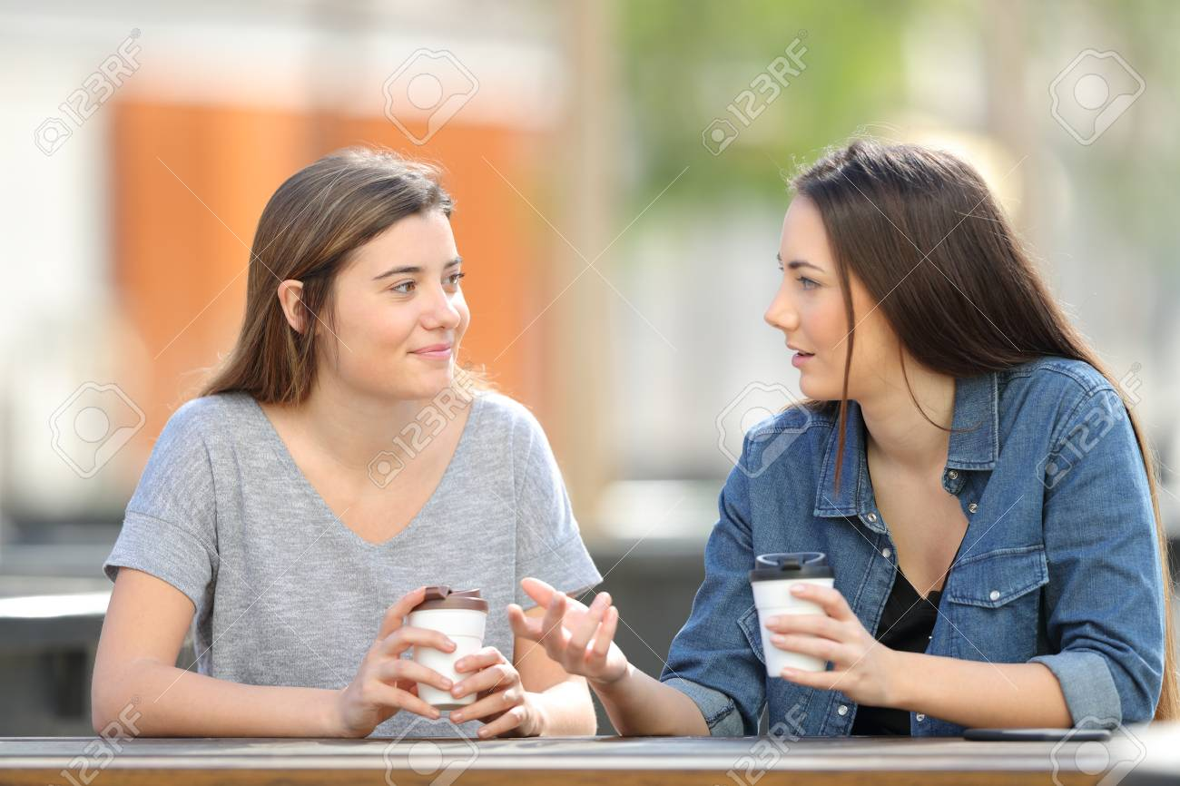 Two casual friends talking in a park drinking coffee - 120969464
