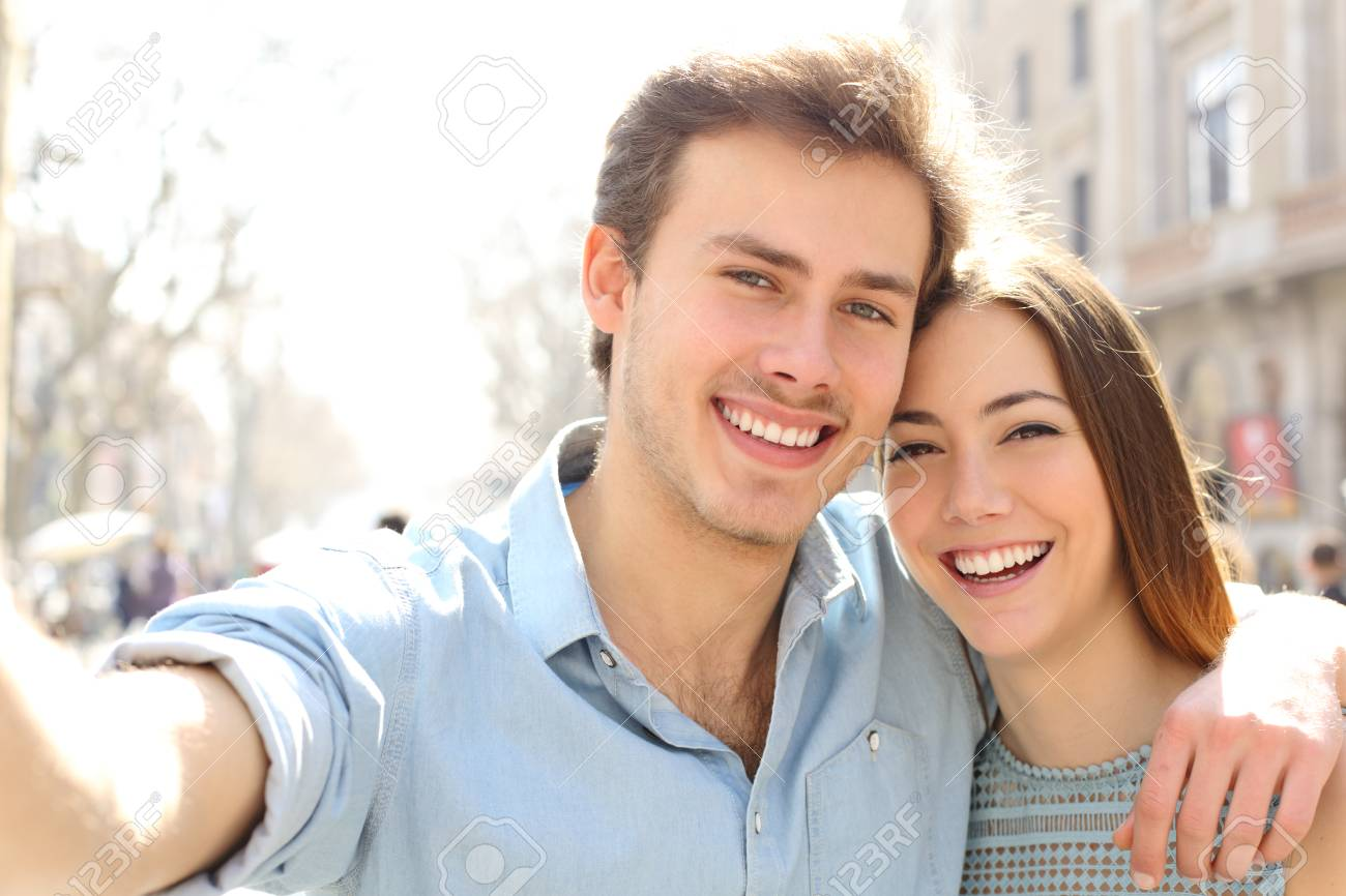 Happy couple are taking selfies in the street on summer holiday in a big city - 123603096