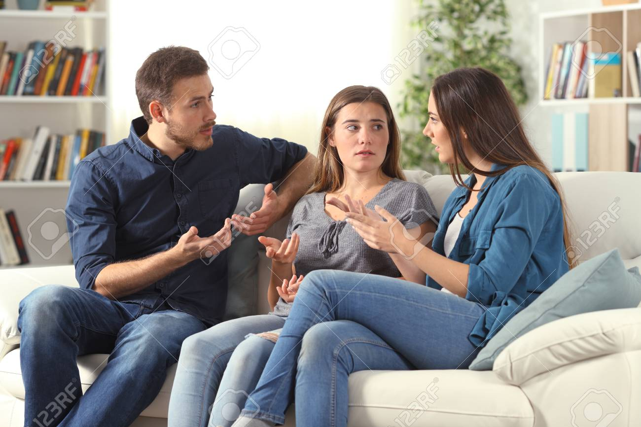 Three serious friends talking sitting on a couch in the living room at home - 123603237