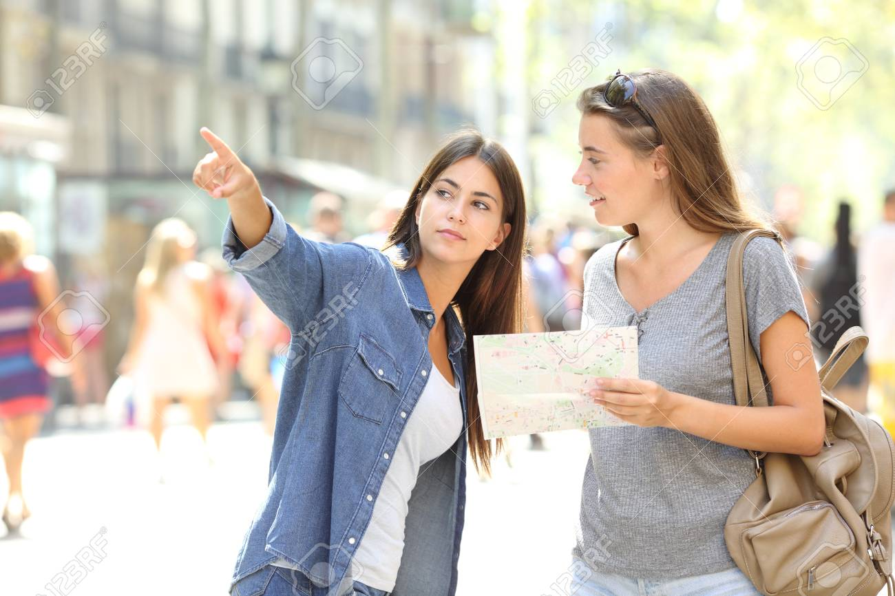 Lost tourist asking for help from a pedestrian in the street - 123603249
