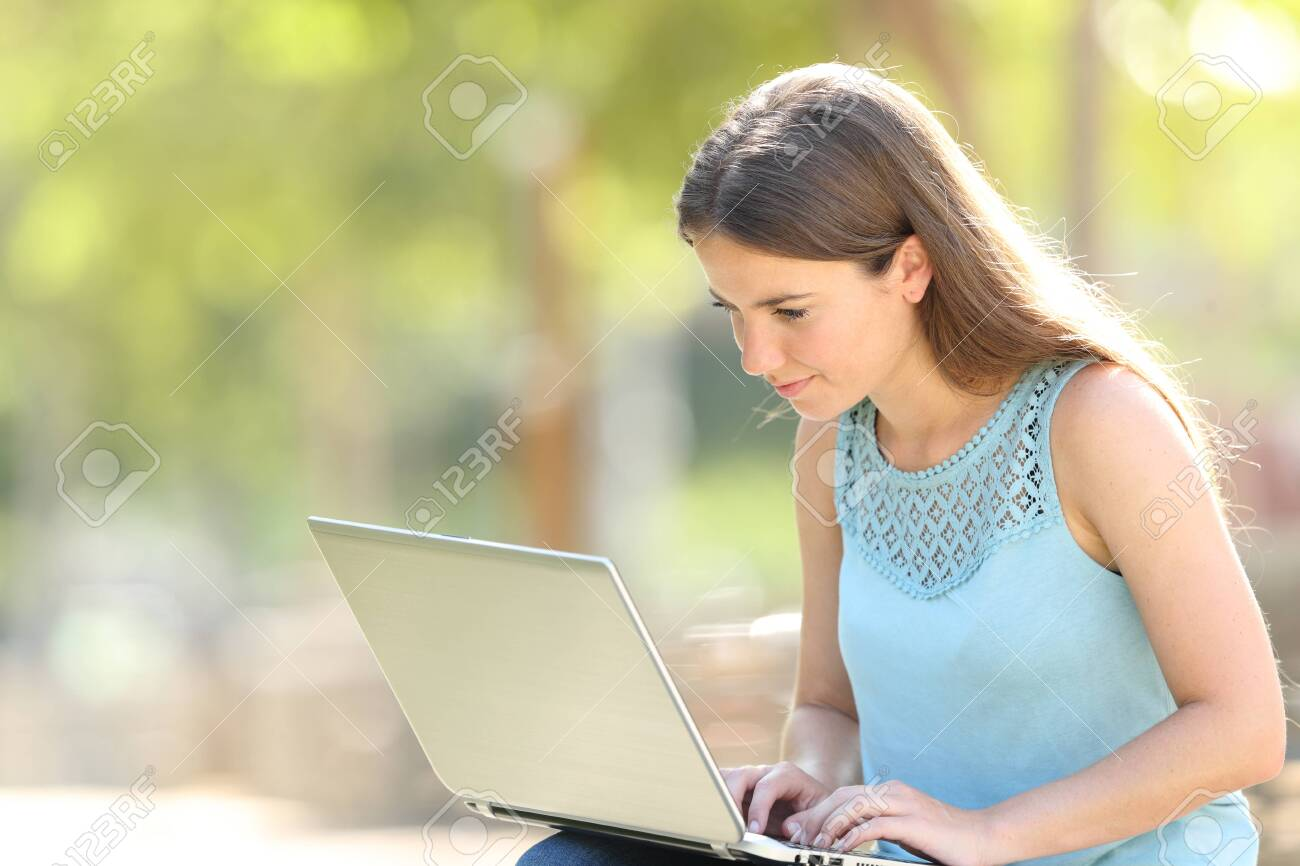 Serious woman sitting in a park using a laptop to search online content - 126564383