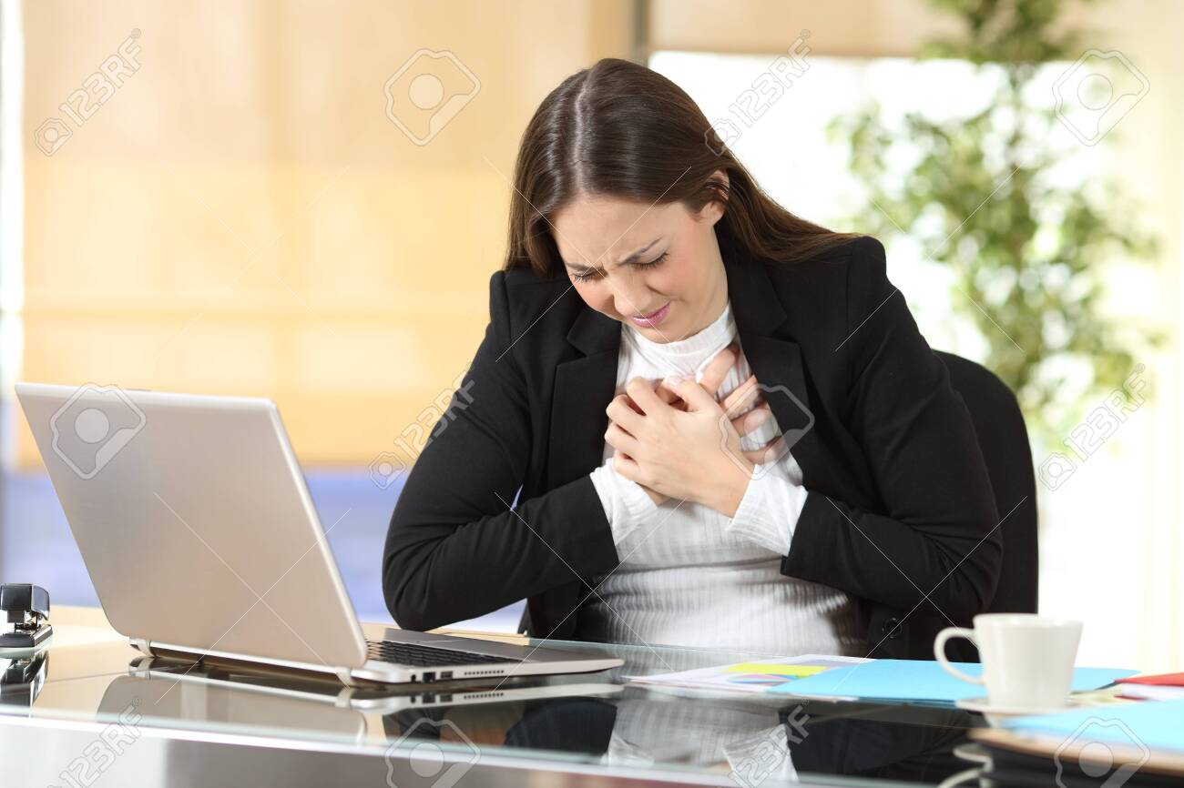 Young businesswoman suffering chest ache sitting alone at office - 126578140