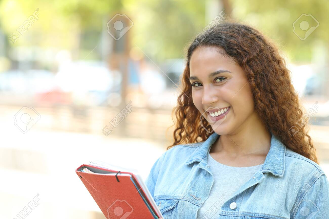 Happy mixed race student posing looking at camera standing in a park - 128723579