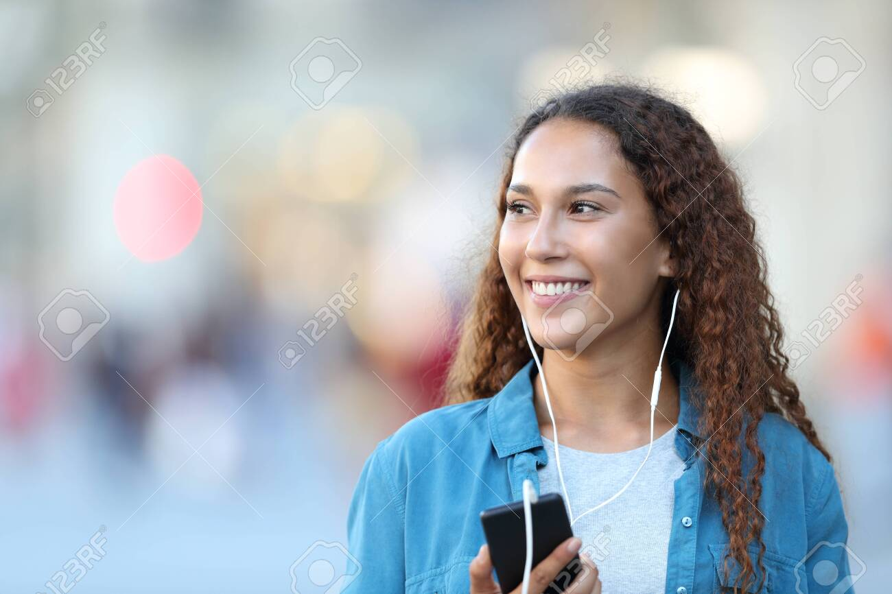 Front view portrait of a mixed race woman listening to music looking at side in the street - 129968499