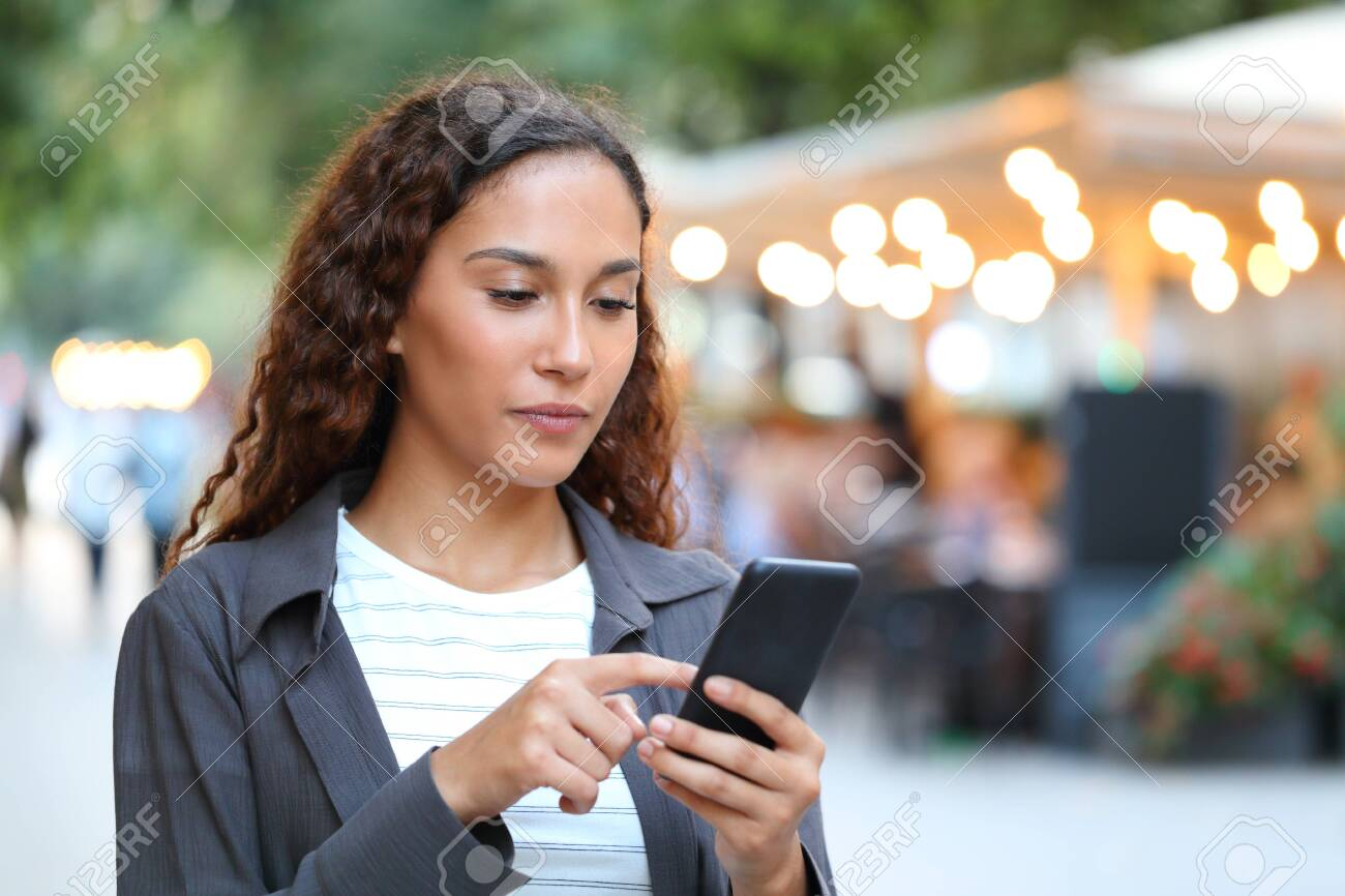 Serious mixed race woman using smart phone walking in the street with city lights in the background - 129969001