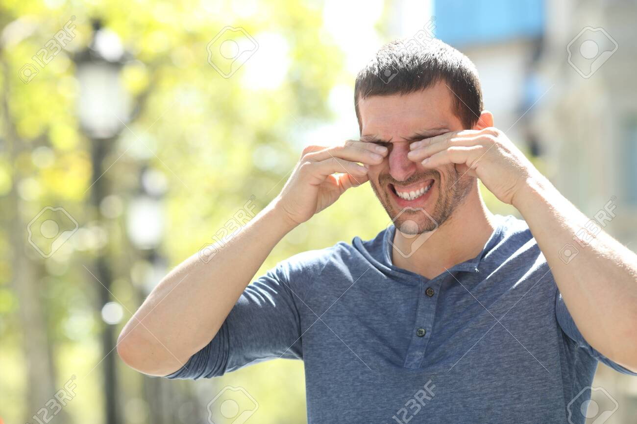 Adult man scratching itchy eyes with both hands standing in the street - 131834875