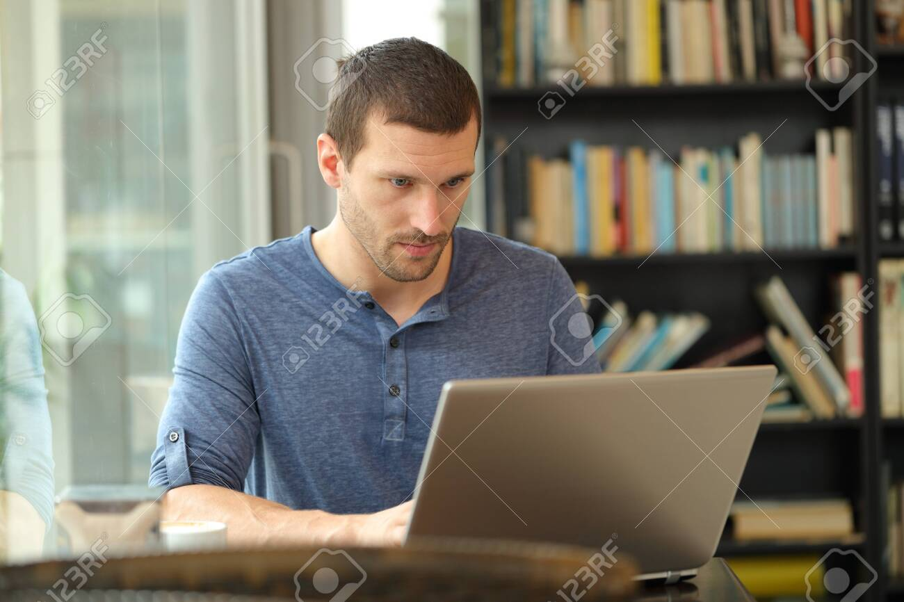 Serious man using a laptop entering data sitting in a coffee shop or home - 132378631