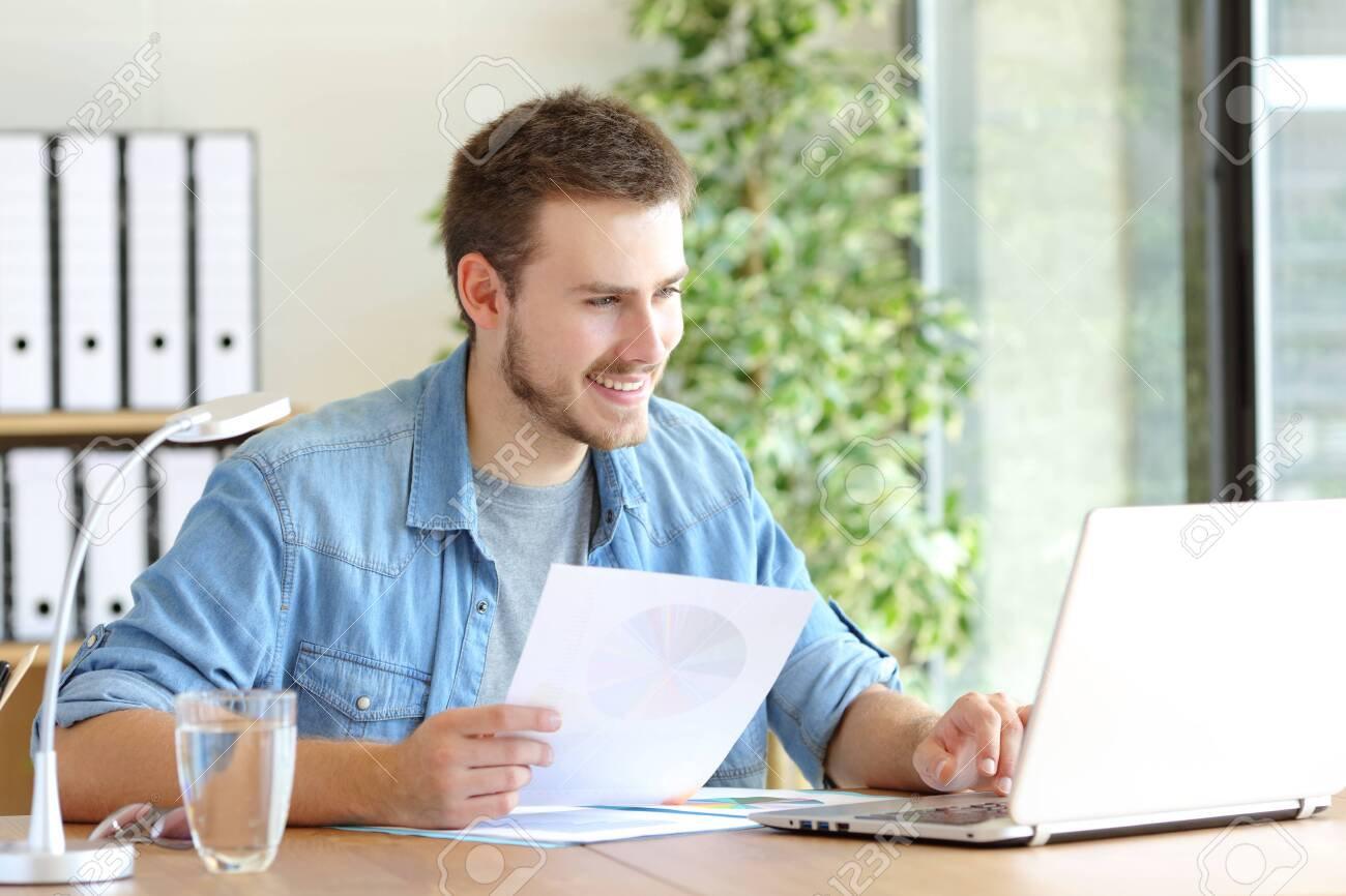 Casual happy entrepreneur working using laptop holding document comparing data at office - 133951673