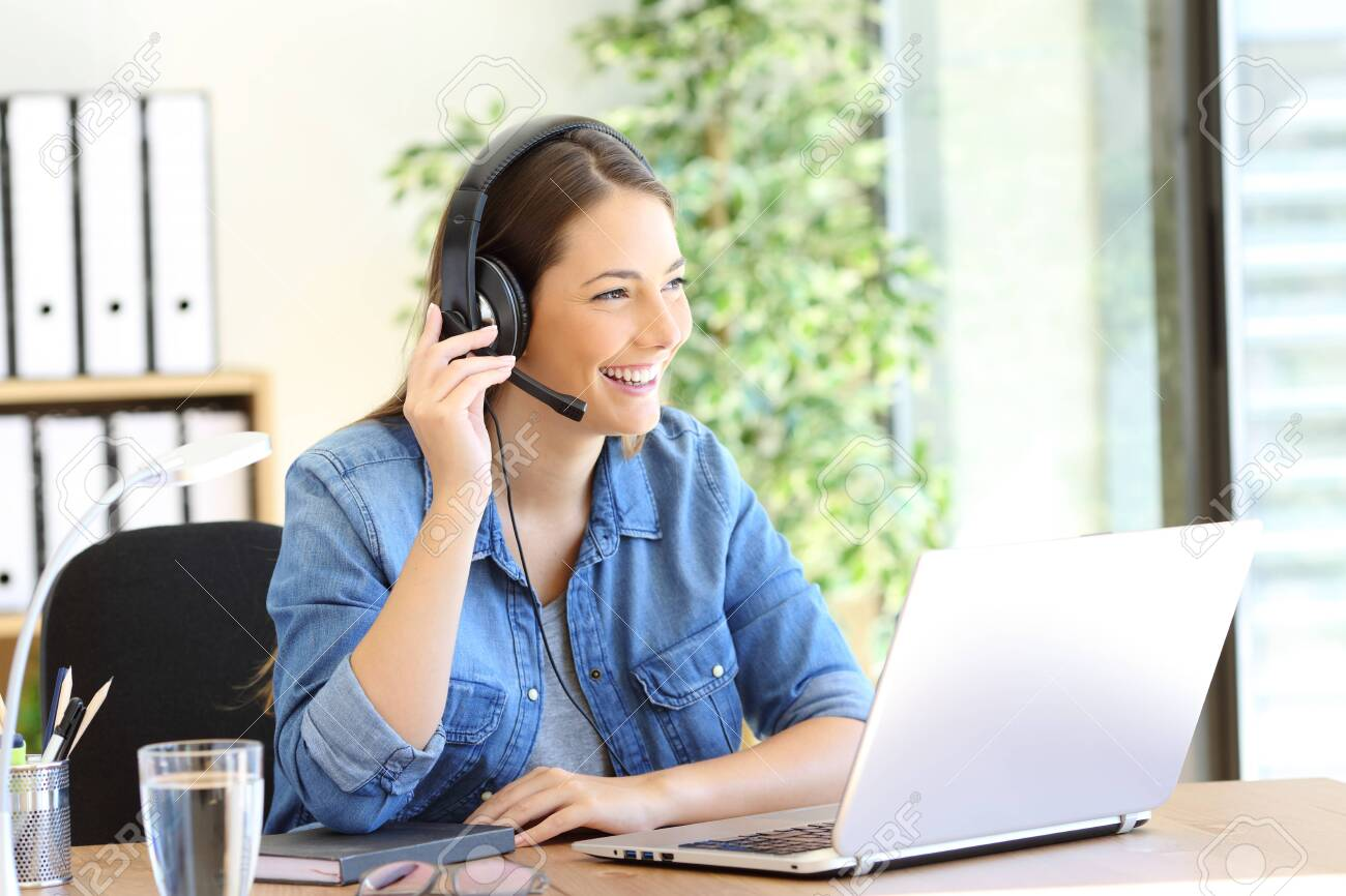 Happy tele operator woman attending call looking away at office - 133951749