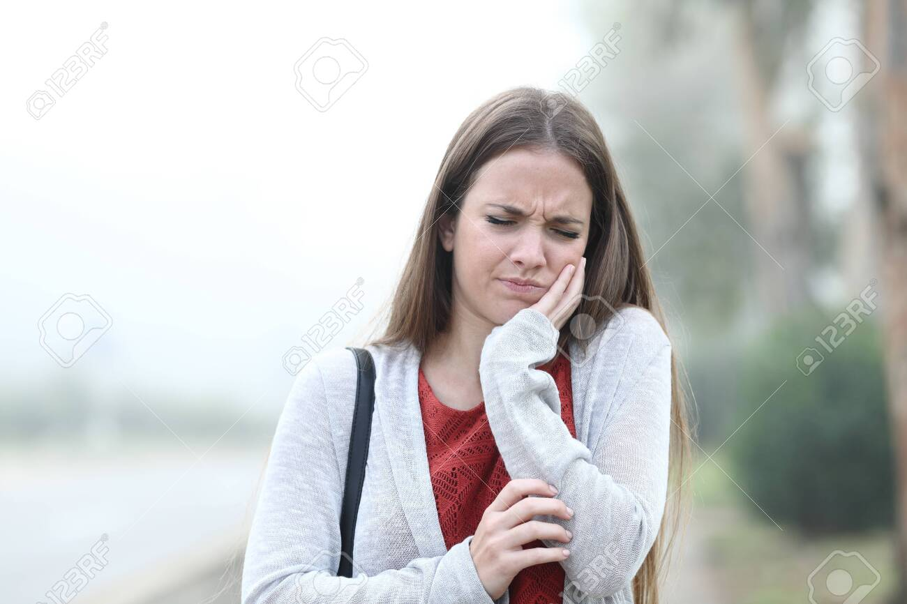 Front view portrait of an woman suffering tooth ache a foggy day - 133952278