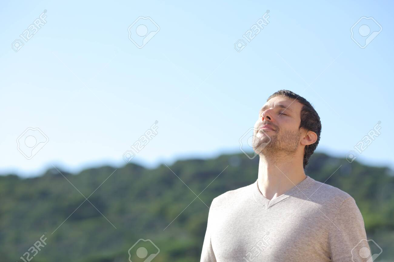 Relaxed man breathing fresh air near the mountains with a blue sky in the background - 141829656