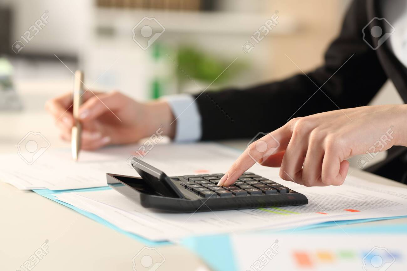 Close up of executive woman hands calculating with calculator on a desk at the office - 144254428